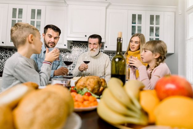 Счастливая семья деда, молодых родителей и детей мальчик и девочка празднуют день благодарения на уютной кухне