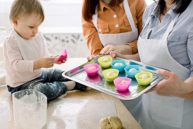 Счастливая любящая семья готовит пекарню вместе. женщины в белых фартуках пекут кексы и держат противень с силиконовыми формами для кексов. маленькая девочка держит форму кекс
