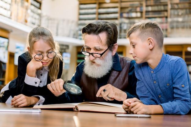Дедушка сидит с внуками за столом в библиотеке, читает и рассказывает книгу