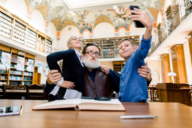 Старый бородатый дедушка и внуки сидят за столом в винтажной библиотеке, позируя для селфи фото на смартфоне, развлекаясь, взволновавшись и гордясь