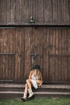 納屋の前でエレガントなドレスを着て腕を組んで立っている女の子のグループ