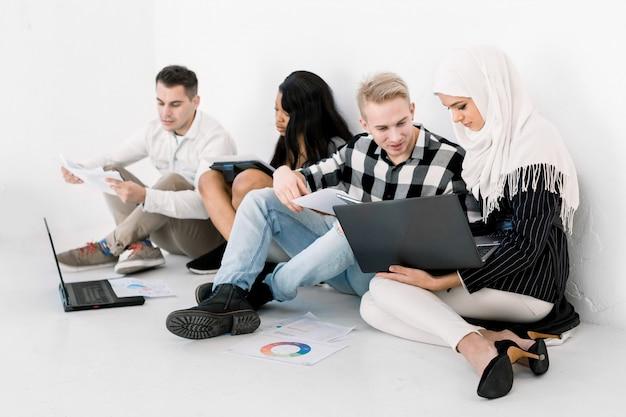 Группа из четырех веселых многонациональных групп студентов колледжа или деловых людей