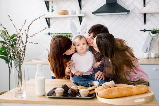 Милая маленькая девочка с кроличьими ушами на голове и ее красивая мама, тетя и бабушка едят кексы, которые они держат в руках. пасхальные каникулы или день матери