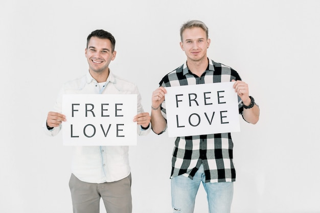 Два красивых кавказских мужчины, лгбт-активисты, борющиеся против дискриминации геев, свободной равной любви, держат плакаты с лозунгами