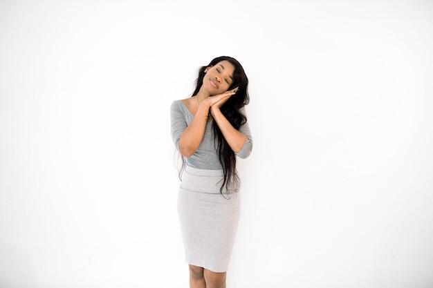 灰色のドレスで疲れたアフリカ系アメリカ人女性は、手を組んで頭を入れて、眠そうな空想