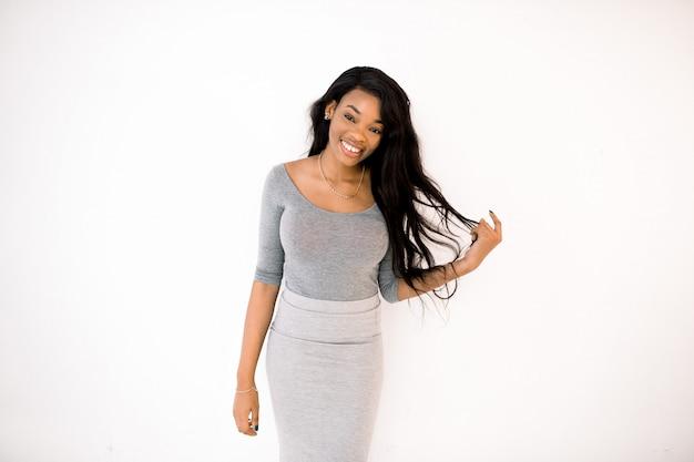 白い背景に分離された灰色のドレスで笑顔のアフリカの若い女性の肖像画