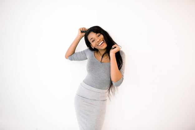 幸せな笑顔でスタジオでポーズをとる長いストレートの髪を持つ陽気な若いアフリカ女性の肖像画