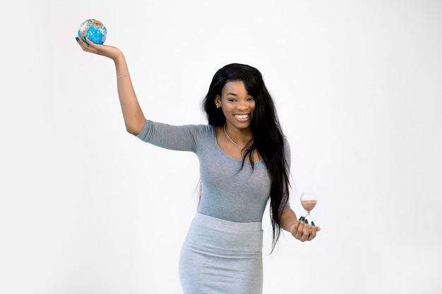 Довольно африканская девушка в сером платье держит земной шар в одной руке и песочные часы в другой, улыбаясь и стоя на белом фоне