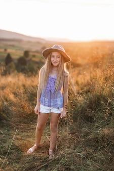 Красивая маленькая белокурая девушка в шляпе стоит в поле