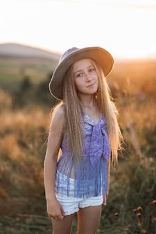 Милая маленькая девочка с длинными светлыми волосами, в коричневой шляпе, позирует в поле