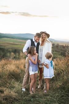 Счастливая улыбающаяся молодая семья, отец, мать и две маленькие дочери веселятся на свежем воздухе