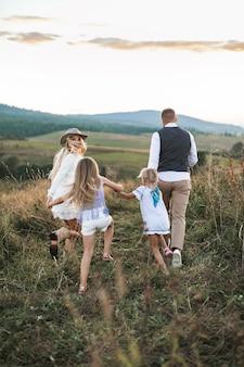 Семья с двумя маленькими дочерьми бегает и веселится на диком летнем поле