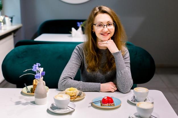 魅力的な幸せな若い女性に座って、カフェでデザートを食べています。カフェで彼女の友人を待っている女性