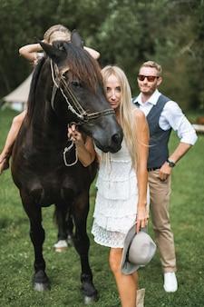 Молодая счастливая улыбающаяся семья с лошадью