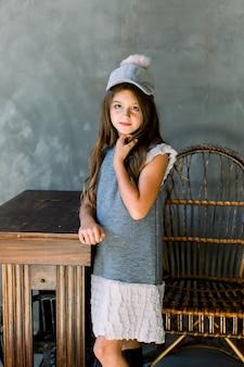 健康な髪の幸せなファッションモデルは灰色の壁に木製のテーブルに手を置く