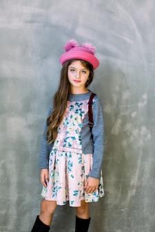 Портрет маленькой модной малышки в розовой кепке и платье с цветами и коричневым рюкзаком на серой стене