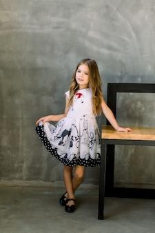 灰色の壁の椅子に手を置いたフルハイトの小さな女の子の肖像画