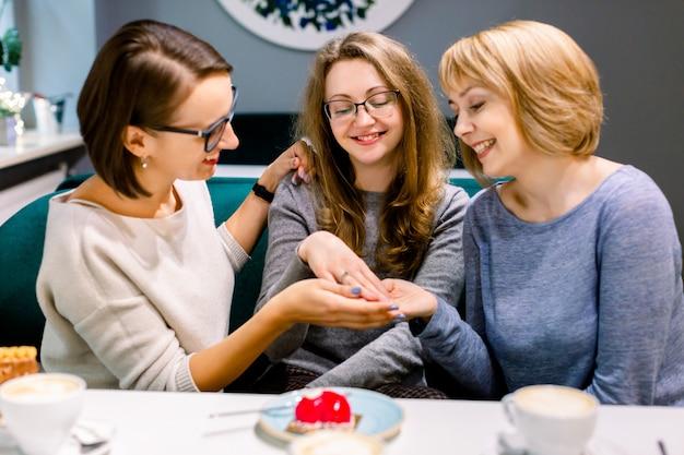 Милая молодая женщина показывая обручальное кольцо к ее двум лучшим друзьям в праздновать кафа