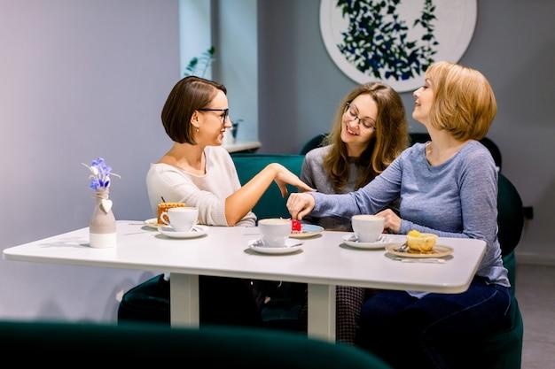 Три подруги весело и едят десерты с кофе в пекарне или кондитерской. красотка показывает свои новые маникюрные ногти для своих друзей