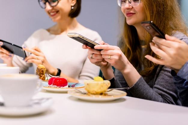 Технологии, образ жизни, дружба и люди концепции - три счастливые молодые женщины со смартфонами делают фотографии своих кофейных чашек и десертов в кафе в помещении