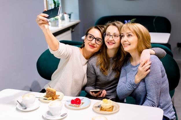 Три молодые красивые женщины сидят в кафе в помещении, счастливы, веселятся, улыбаются, смотрят на смартфон, делают селфи фото, кокетливые