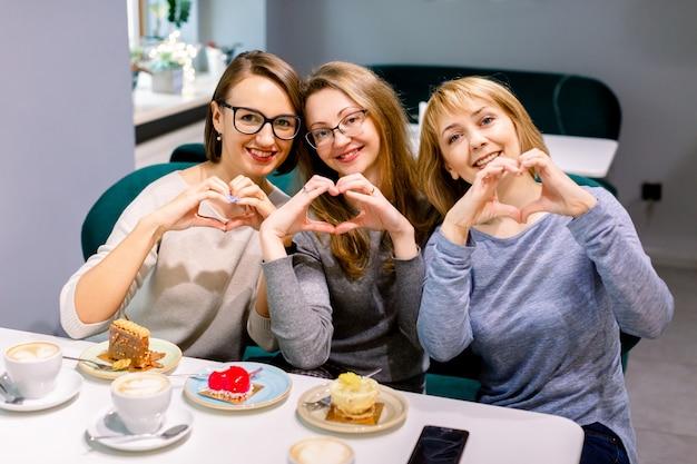 Три красивые подруги, счастливо улыбаясь, делая знак сердца своими руками, сидя в кафе в помещении