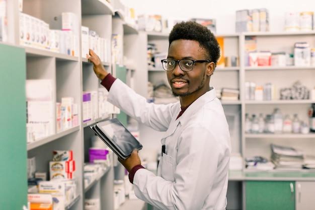 Афро-американский мужской аптекарь используя цифровую таблетку во время инвентаря в фармации.