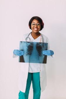 Молодая усмехаясь афро-американская женщина-врач в медицинской одежде держит рентгеновский снимок пациента