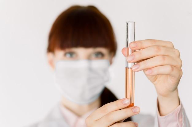 Закройте вверх по портрету доктора маленькой девочки, ученого лаборатории, в белом пальто и медицинской маске, смотрящ испытания в стеклянной пробирке на белой предпосылке. сосредоточиться на руках с колбой с красной жидкостью