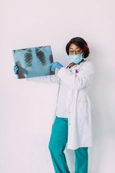 Молодой усмехаясь доктор афроамериканца в медицинской маске держа рентгеновский снимок пациента