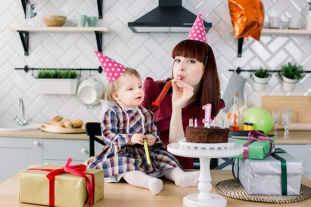 赤ちゃんと母親がパーティーホーンに吹き