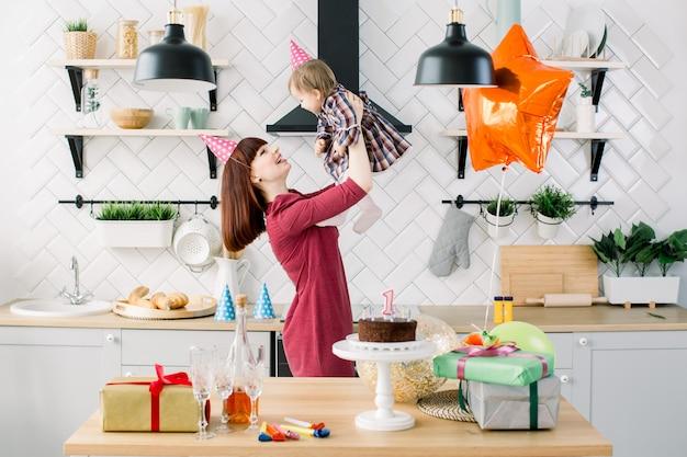 幸せな子供の誕生日。母親、赤ちゃんの娘、風船、ケーキ、ギフト