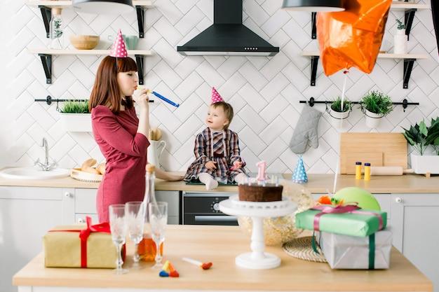 母は家庭の台所で彼女の女の赤ちゃんの最初の誕生日を祝っています。彼女のかわいい母親がパーティーホーンに吹いている間笑顔と楽しい女の赤ちゃん