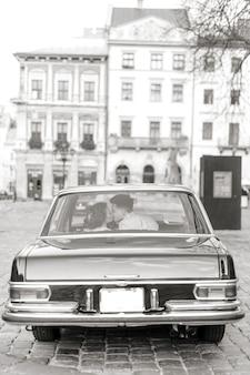 かなりの花嫁とハンサムな新郎のキスとレトロな車でハグします。結婚式の日、レトロなスタイル、旧市街の中心。