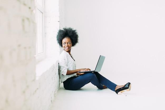 Молодой афроамериканец бизнес женщина, используя ноутбук, сидя на полу возле большого окна