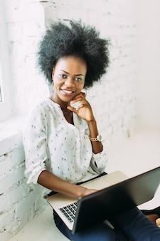 Молодая усмехаясь афро-американская бизнес-леди используя компьтер-книжку, сидя на поле