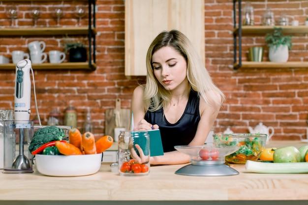 Счастливая красивая белокурая женщина стоя в ее кухне и писать список покупок на тетради дома. здоровая пища - овощной салат. рацион питания. концепция диеты. здоровый образ жизни. готовим дома.