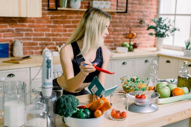 Молодая женщина приготовление салата и проведение красный перец на кухне. здоровая пища - овощной салат. рацион питания. концепция диеты. здоровый образ жизни. готовим дома. готовить пищу