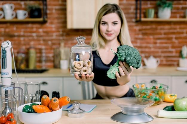 Молодая женщина в черной спортивной одежде, выбирая между брокколи или нездоровой пищи, бублики. здоровая чистая концепция еды вытрезвителя. вегетарианская, веганская, сырая концепция. копировать пространство