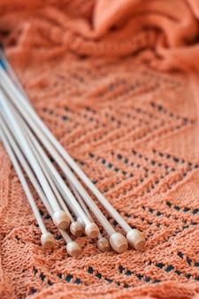 Много деревянных спиц на оранжевом вязаном пледе