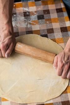 セルの表面に生地を混練男性の手のクローズアップ