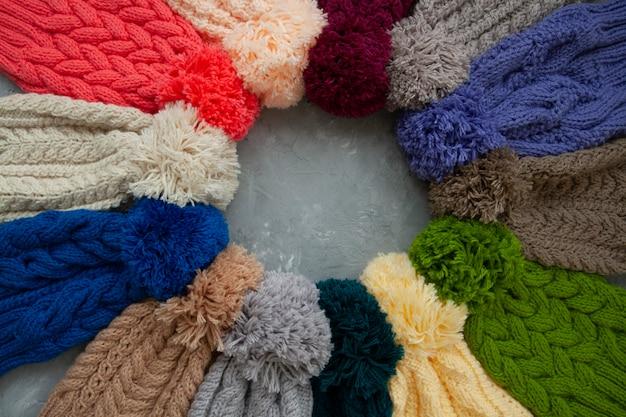 Много ярких шляп лежат на сером бетонном фоне