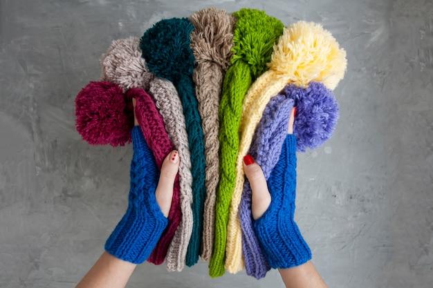 Руки молодой красивой женщины в голубых варежках держит много цветных ярких теплых зимних шапок