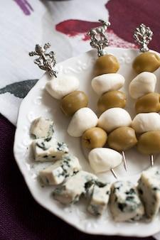 Тарелка вкусных закусок на скатерть. канапе с моцареллой и оливками, кусочки сыра рокфор.