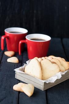 Красная чашка и печенье сердца на черной поверхности