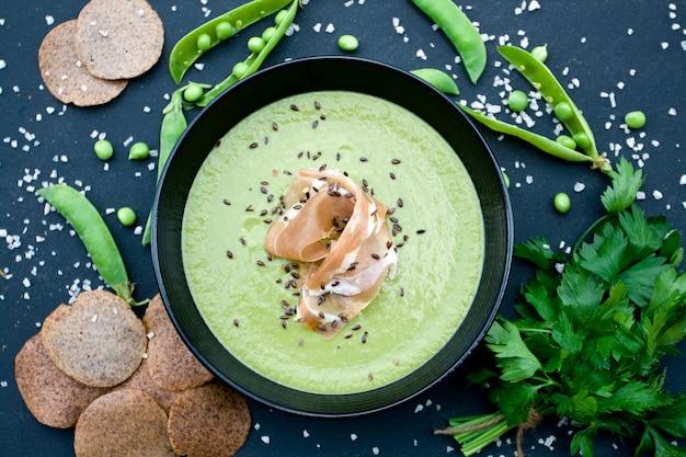 ハムとエンドウ豆の黒いテーブルの上の健康的なグリーンスープ