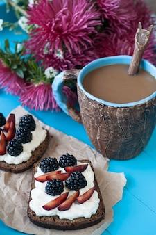 Бутерброды со сладким сыром и ягодами, чашка кофе и букет астр на синей деревянной поверхности