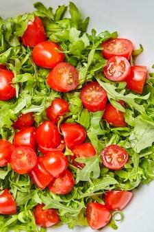 Красные половинки помидоров черри со свежими зелеными листьями рукколы (рукколы). овощной салат, вид сверху