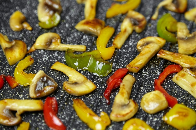 ノンスティックコーティングを施したフライパングリル鍋でキノコと野菜を調理します。シャンピニオンでカラフルなピーマンを焙煎