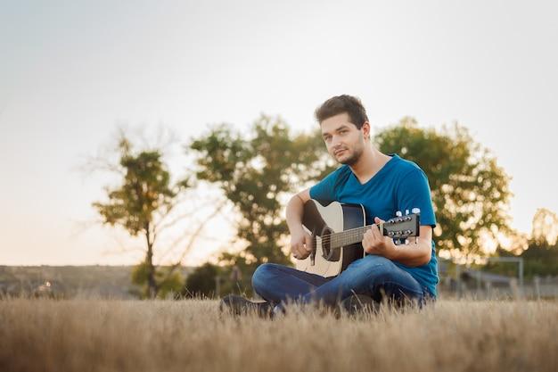 外でギターを弾く陽気な若者。ポジティブな雰囲気のミュージシャン。